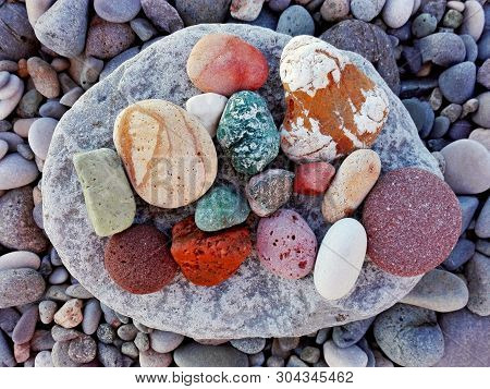Pile Of Colorful Pebble Stones On Rock Pattern Background. Different Forms Multicolor Pebbles (green