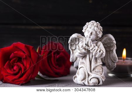 Mourning Concept. Little Angel, Red Roses And Burning Candles On Grey Textured Background. Card For