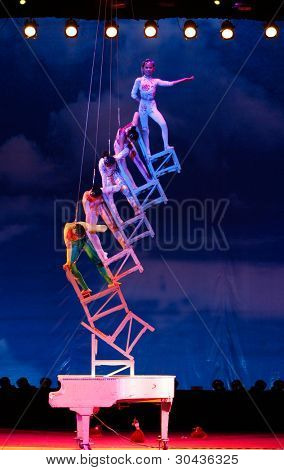 SHANGHAI, CHINA - NOVEMBER 28: A team of of gymnasts from the world famous Shanghai acrobats perform a balancing act on stacked chairs for tourist on stage on November 28, 2011 in Shanghai, China.