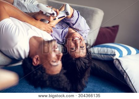 Young smiling couple playing videogames at home. poster