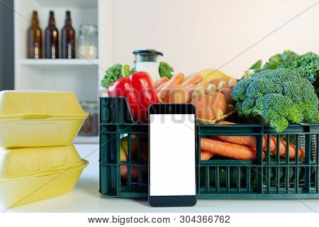 Food Delivery Service - Smartphone In Front Of The Box Of Groceries