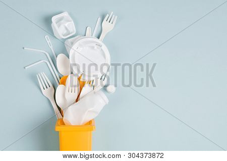White Single Use Plastic In Garbage Bin On  Blue Background. Concept Of Recycling Plastic. Flat Lay,