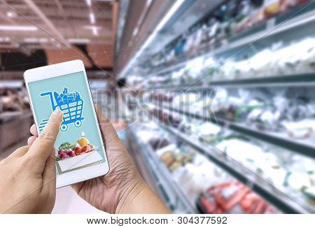 Online Grocery Shopping Concept: Woman Hand Holding Smart Phone For Ordering Food Onscreen With Icon