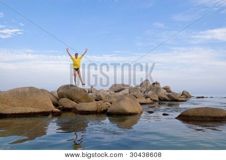 Sea.The young man costs(stands) on one leg(foot) on a stone.