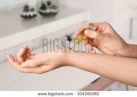 Woman Applying Essential Oil On Wrist Indoors, Closeup