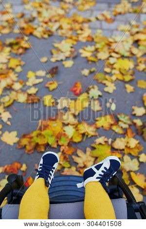 Little Girl In Bright Stylish Clothes Sitting In Pushchair Outdoors On A Fall Day. Autumn Walks With