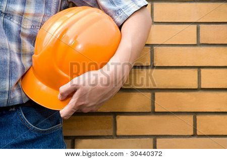 The  bricklayer on a background of a brick wall.