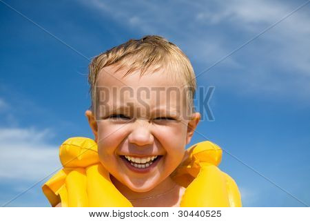 The smiling boy in a life jacket on a beach.