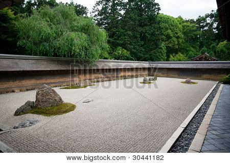A Zen Rock Garden in Ryoanji Temple.In a garden fifteen stones on white gravel. Kyoto.Japan.Evening.