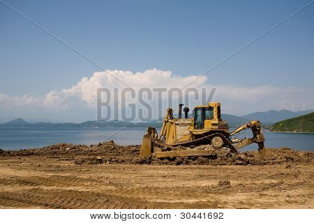 The bulldozer on a building site.On a background the sea.