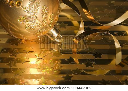 Christmas gold baubles(ball,ribbon,stars) on a gold background.