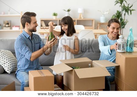Happy Young Family Unpack Boxes Moving To New Home
