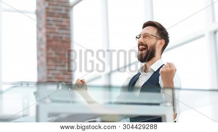 Very Happy Businessman Sitting At The Office Desk