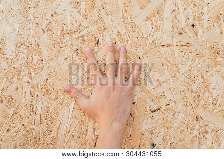 pressed sawdust in the board. Hand on the board of compressed sawdust. background of pressed wooden sawdust. poster