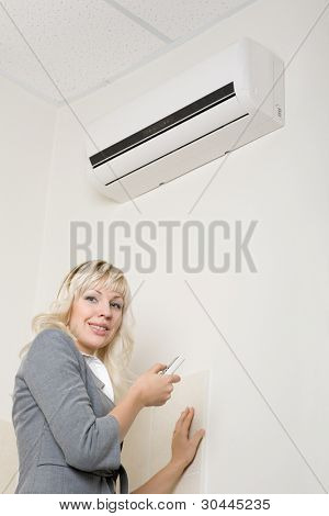 Attractive girl includes air conditionier in the office.