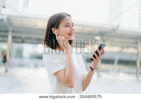 Women Are Listening To Music From White Headphones. And Using Hands Touch To Use Various Functions,
