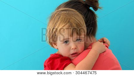 Side View Of Young Mom Cuddling Sad Kid Looking At Camera Isolated On Blue Background