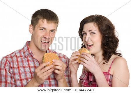 Girl and a guy eating hamburgers/ Isolated on white.