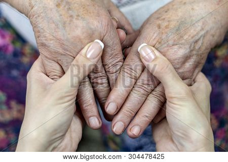 Hands Of Old Grandmother In Young Hands Of Granddaughter