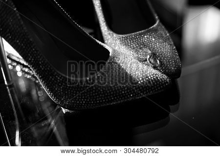 poster of wedding rings on the brides shoes. Wedding. Decor. Brides shoes. Wedding brides shoes and rings. Wedding white shoes