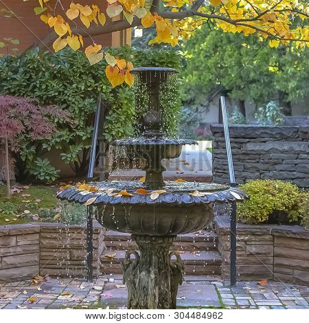 Square Beautiful tiered fountain on a garden with lush trees and plants in autumn poster