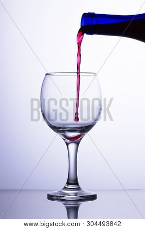 The First Drop Of Wine Falls Into An Empty Transparent Glass. A Jet Of Red Wine Flows Into A Glass F