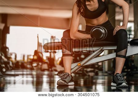 Working Out With Dumbbell Weights At The Gym.fitness Women Exercising Are Lifting Dumbbells With A W