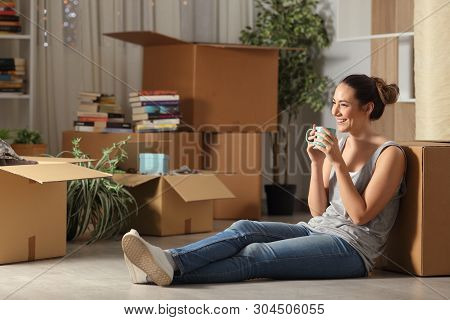 Happy Tenant Resting Drinking Coffee Moving Home Sitting On The Floor In The Night