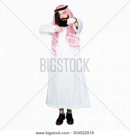 Arabian business man with long hair wearing traditional keffiyeh scarf Punching fist to fight, aggressive and angry attack, threat and violence