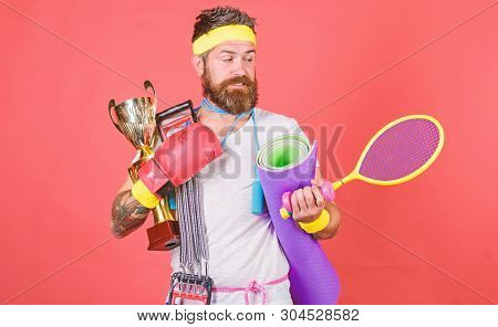 Man Bearded Athlete Hold Sport Equipment Jump Rope Fitness Mat Boxing Glove Expander Racket And Gold