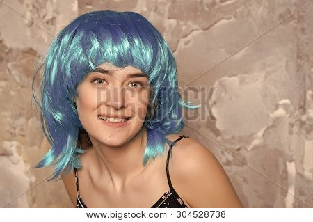 Freak Concept. Lady On Smiling Face Posing In Blue Wig, Concrete Wall Background. Woman With Blue Ha