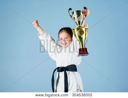 Small Girl With Champion Cup. Martial Arts. Winner Little Girl In Gi Sportswear. Practicing Kung Fu.
