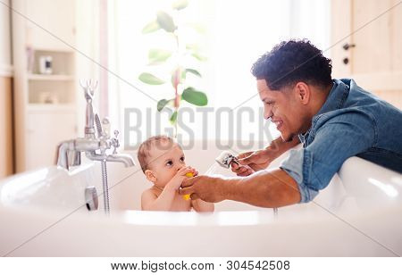 Father Washing Small Toddler Son In A Bathroom Indoors At Home.
