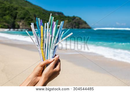 Hand Holding Heap Of Used Plastic Straws On Background Of Clean Beach And Ocean Waves. Plastic Ocean