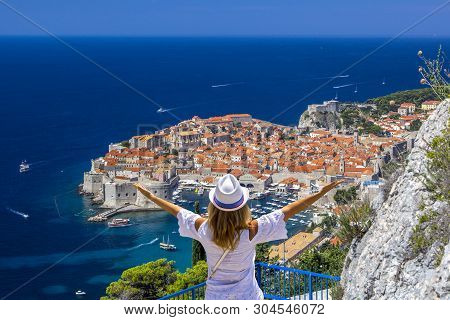 Happy Girl Enjoys View Of Old Town (medieval Ragusa) And Dalmatian Coast Of Adriatic Sea In Dubrovni