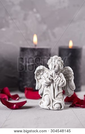 Mourning  Background. Little Angel,  Petals Of Red Roses And Burning Candles On Grey Textured Backgr