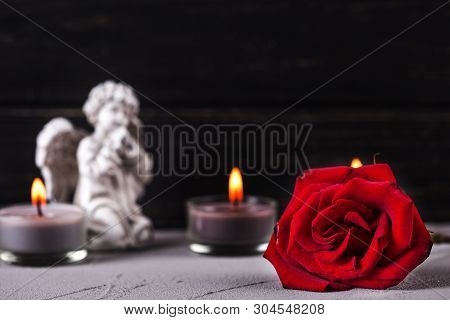 Mourning Concept. Little Angel, Red Rose And Burning Candles On  Dark Background. Card For Mourning,