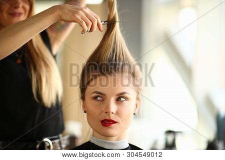 Hairdresser Cutting Hair To Blonde Woman Portrait. Woman With Ponytail Getting Haircut With Scissors