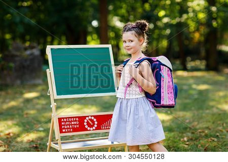 Happy Little Kid Girl Standing By Desk With Backpack Or Satchel. Schoolkid On First Day Of Elementar