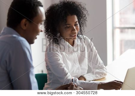 African American Businesswoman Mentor Helping Male Trainee With Project