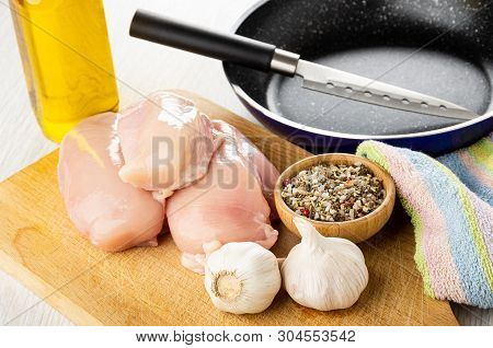 Kitchen Knife In Frying Pan, Bottle Of Vegetable Oil, Pieces Of Raw Chicken Breast, Garlic, Bowl Wit