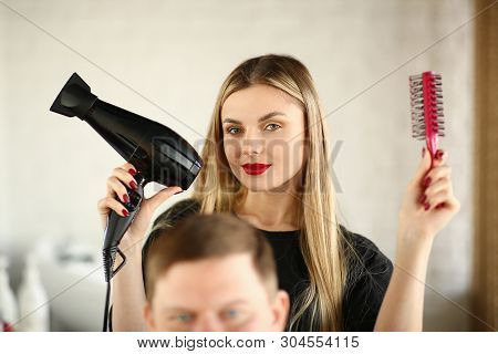 Blonde Hairstylist Showing Blow Dryer And Comb. Woman Hairstylist Using Hairbrush And Hairdryer For