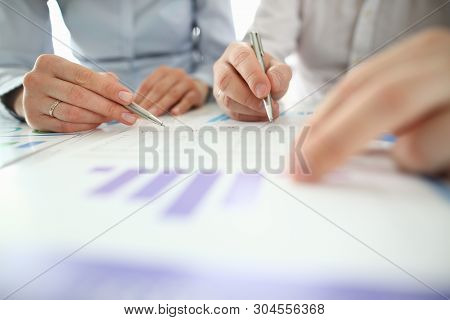 Male And Female Hand Hol Pen Aganist Business Chart Background. Office Work Concept.
