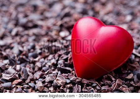 Heart Shaped Chocolate Candy On Crushed Cocoa Nibs. Copy Space