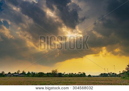 Field Agriculture And Rain Clouds With Sunrays