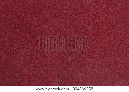 Red rough textured sandpaper background. Macro red sandpaper. poster