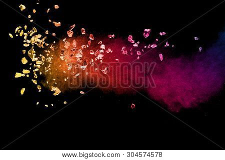 Split Debris Of Colored Stone With Dust Exploding Against Black Background.