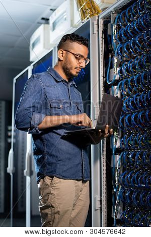Concentrated handsome young Arabian bearded network engineer in glasses standing by network server cabinet and examining errors on laptop