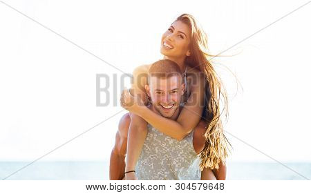 Young Happy And Joyful Caucasian Adult Romantic Couple Doing Piggyback - Boyfriend Carrying Girlfrie
