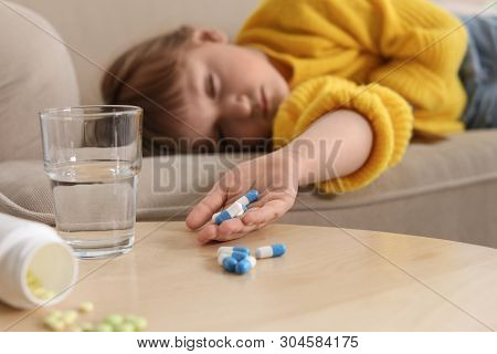 Unconscious little child with pills on sofa at home. Danger of medicament intoxication poster